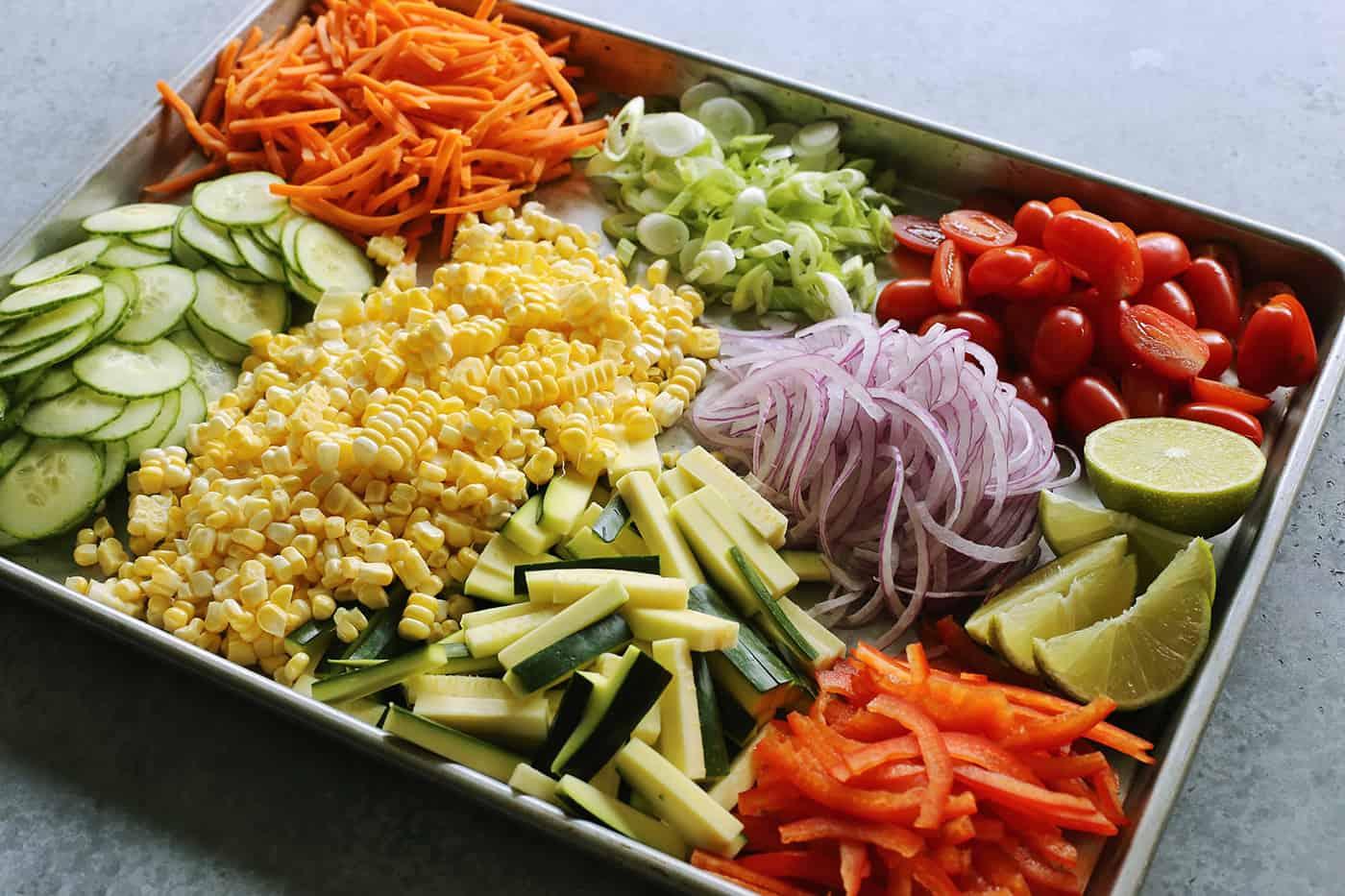 a large rimmed pan full of chopped and sliced fresh vegetables
