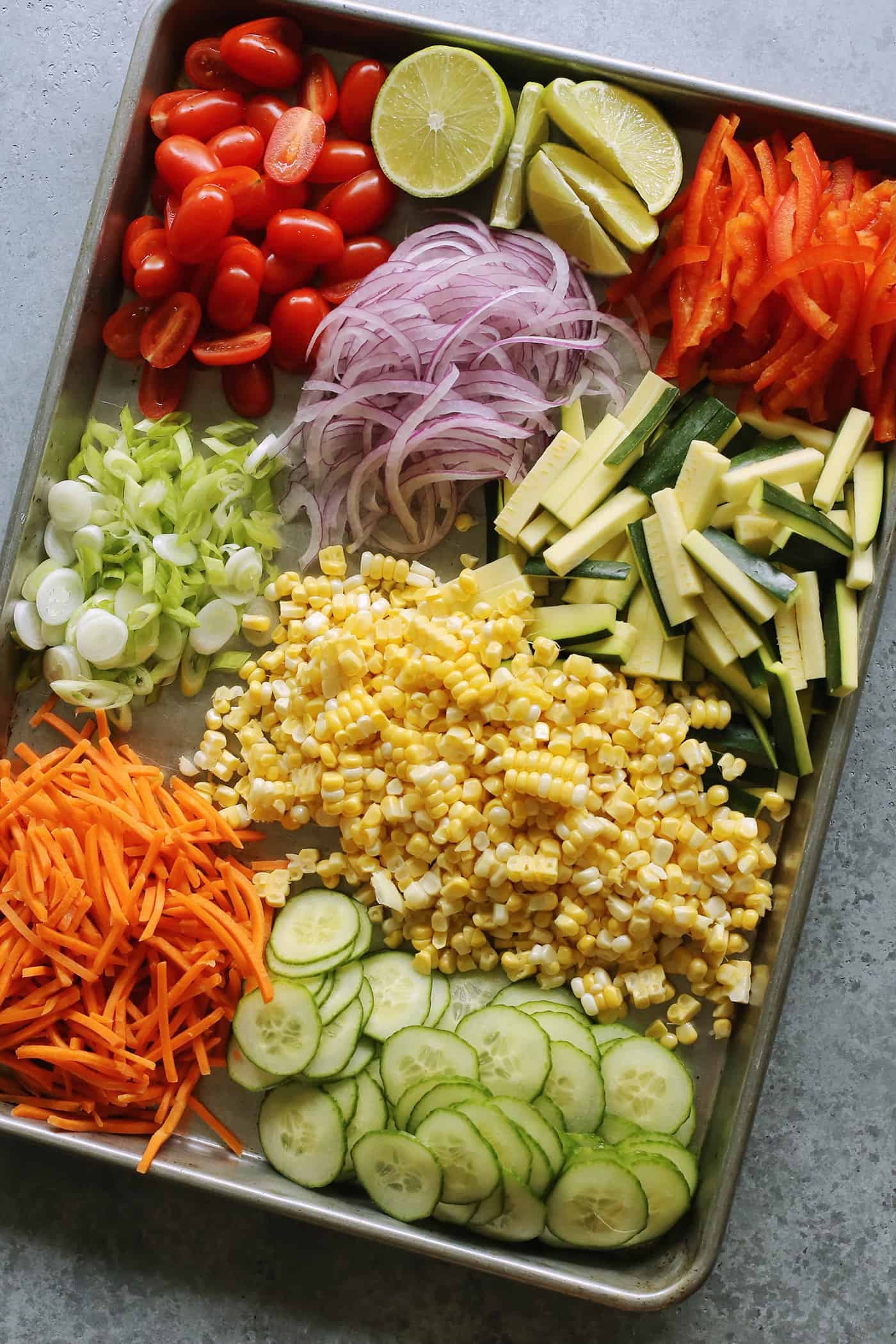 a large rectangular rimmed pan full of chopped and sliced fresh vegetables
