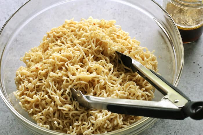 a clear bowl of cooked ramen noodles, with a tongs