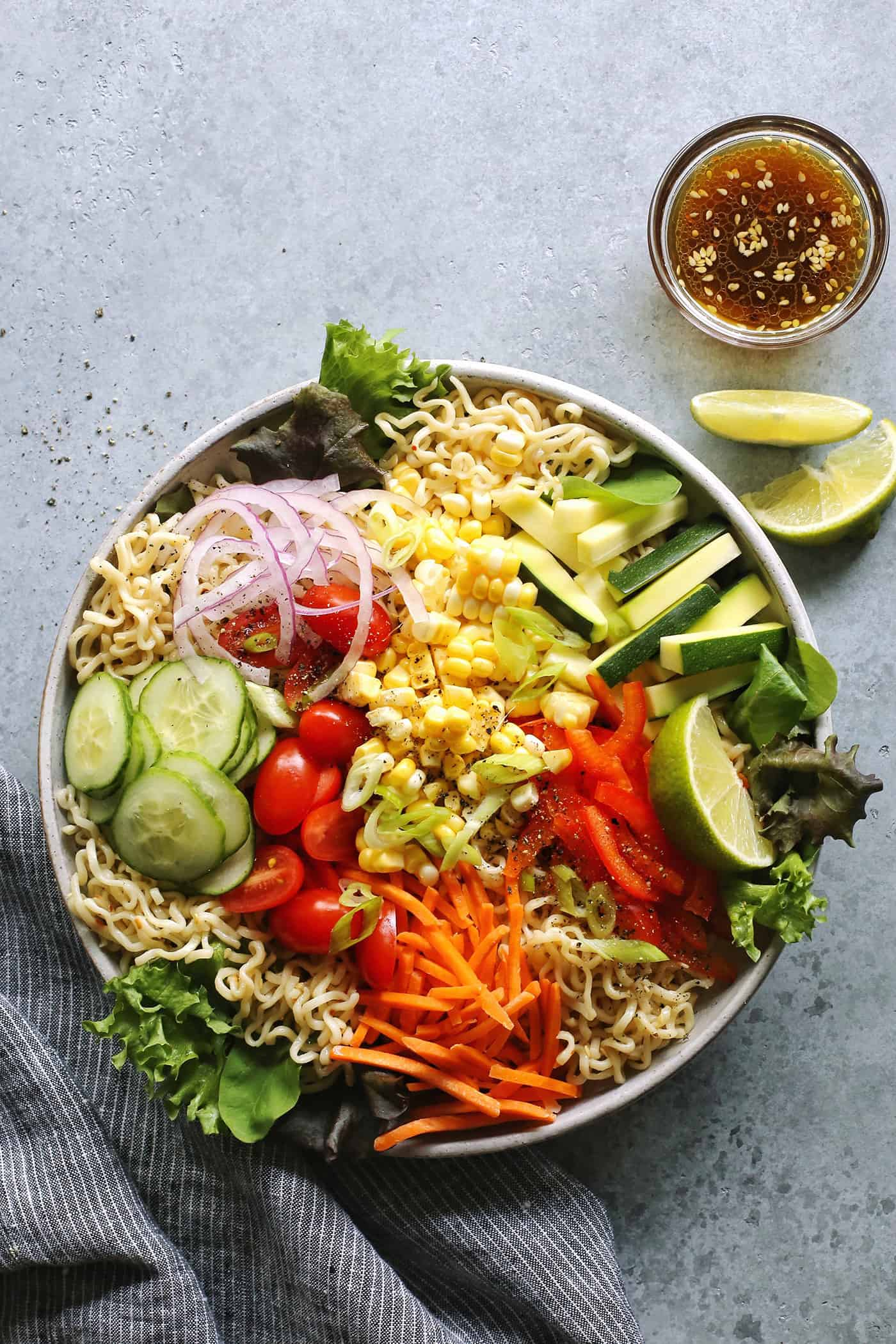 salad ramen in a light gray bowl with a cup of dressing on the side