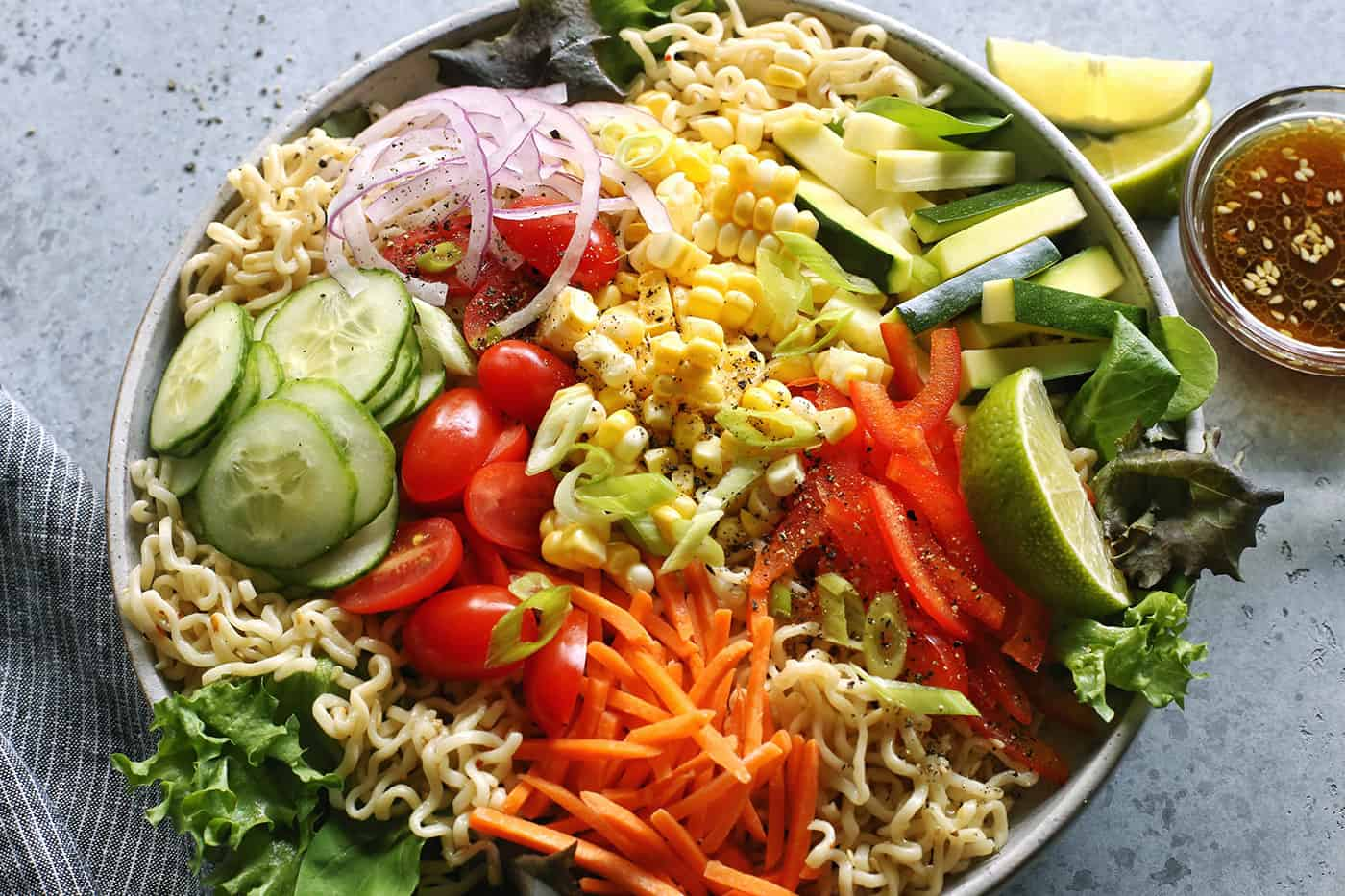 a light gray bowl full of veggies and ramen noodles