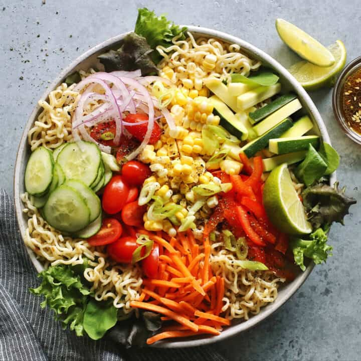 light gray bowl filled with ramen noodles and a variety of fresh vegetables