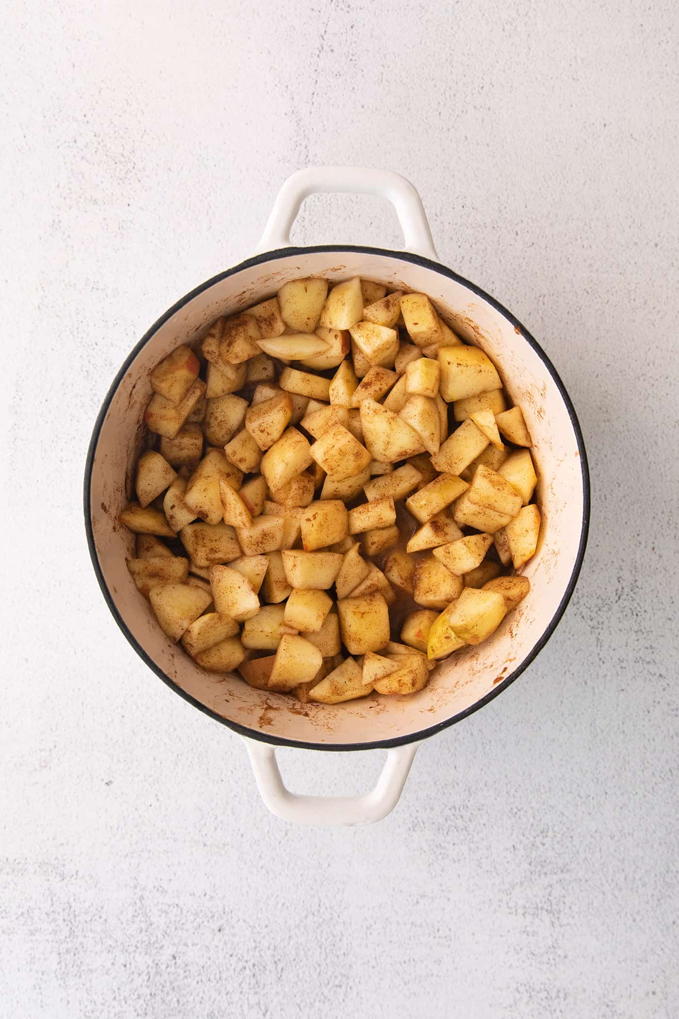 chopped apples with cinnamon in a large white pot