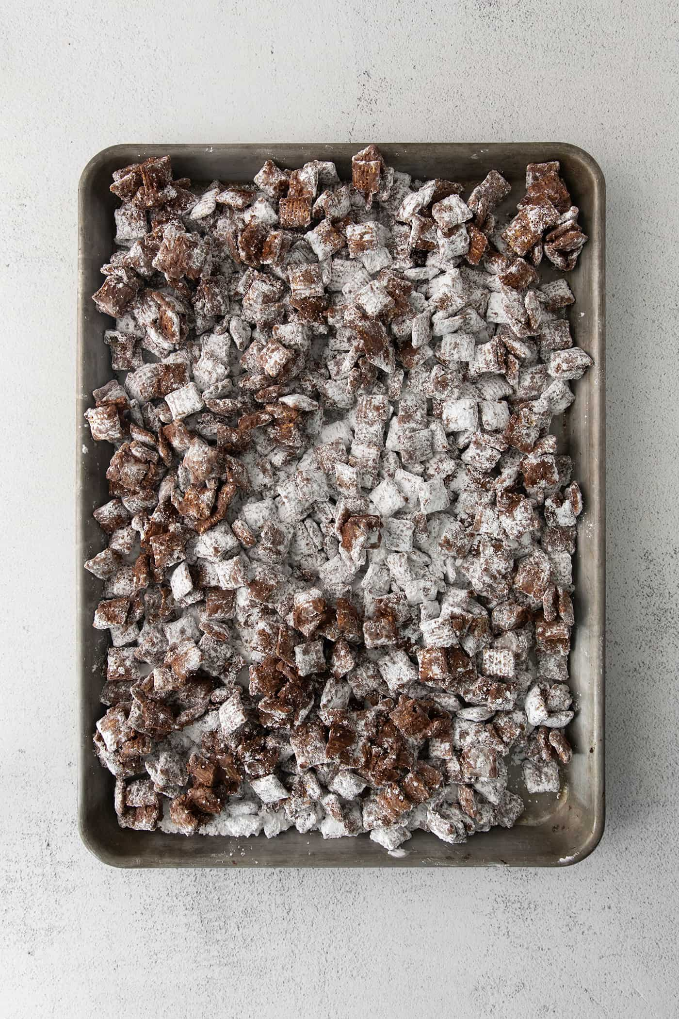Puppy Chow cooling on a large rimmed pan