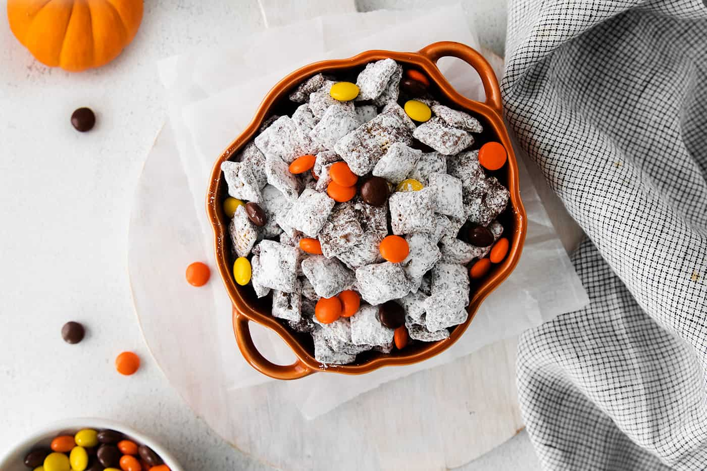 Muddy Buddies with Reese's Pieces candies for Halloween, in a pumpkin bowl